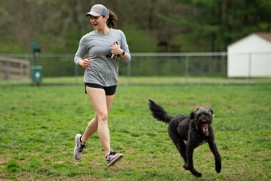 Dyani Edwards, of Mt. Juliet, runs with her dog Deja at Mt. Juliet Bark Park in Mt. Juliet, Tenn., Saturday, March 28, 2020.