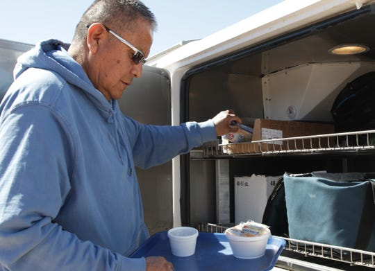 Daniel Lewis, driver for the Newcomb Senior Center, grabs a carton of milk to add to a lunch on March 24 in Newcomb.