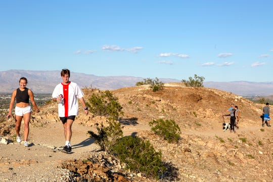 Cassidy Orr, 20, of Palm Desert and Cameron Desnoes, 19, of Indian Wells hike the Homestead Trail in Palm Desert, Calif., on Friday, March 27, 2020. Outdoor exercise is allowed under the shelter-in-place mandate from Gov. Newsom during the virus pandemic. Several hiking trails remain open. Some narrow parts of the Homestead Trail were difficult to maintain six feet for social distancing.