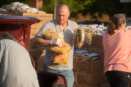 Volunteer Jimmy Allen loads food into a car. Men In Action Outreach, Inc. of Milton partnered with Feeding the Gulf Coast, Inc. and the City of Milton to help bring food in a time of need to families of the community Saturday, March 28, 2020 at the Milton Community Center.