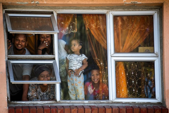 Residents look from their apartment windows reacting to the photographer outside, in Mannenburg, Cape Town, South Africa Saturday, March 28, 2020. South Africa went into a nationwide lockdown to restrict public movements for 21 days in an effort to control the spread of the COVID-19 coronavirus.