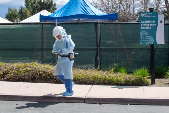 FILE: A Salinas Valley Memorial Hospital employee wears PAPR gear as she heads to the negative pressure tents. March 26, 2020.