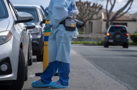 A Salinas Valley Memorial Hospital employee wearing PAPR gear talks with a patient waiting at the drive-thru screening on March 26, 2020. The drive-thru screening is in place to safely evaluate potential COVID-19 cases.