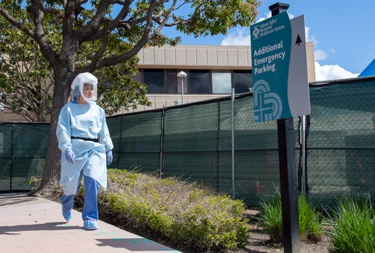 A Salinas Valley Memorial Hospital employee wearing PAPR's gear heads to the line of cars waiting at the drive-thru screening on March 26, 2020. The drive-thru screening is in place to safely evaluate potential COVID-19 cases.