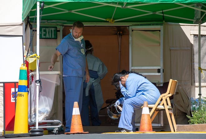 Mitchel Tritt, left, a clinical assistant at Salinas Valley Memorial Hospital stands next to Sandra Ruelas, sits down holding her head after a long shift of seeing many patients come to the drive-thru screening. The three of them are part of the front line of the drive-thru screening that SVMH has established for citizens of Monterey County who are experiencing symptoms tied with COVID-19. March 26, 2020. The drive-thru screening is in place to safely evaluate potential COVID-19 cases.