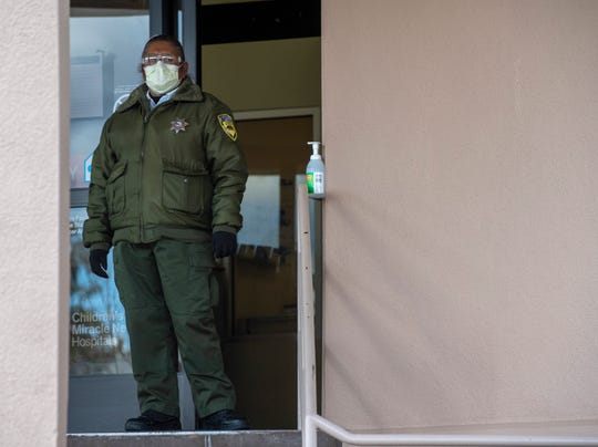 A Salinas Valley Memorial Hospital guard wears a face mask as she waits outside the emergency room March 26, 2020.