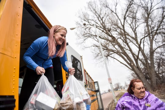 Amanda Pritchard, left, passes out school lunches to students on Thursday, March 26, 2020 in Sioux Falls. The Sioux Falls School District has suspended classes due to the coronavirus but are working with students to provide food and supplies.
