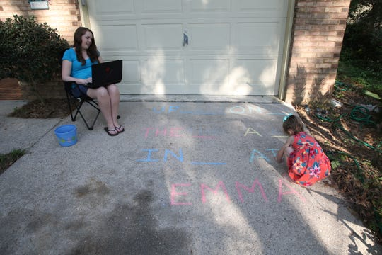 While her daughter Emma, 4, works on writing sight words Brittany Hutto, a 5th grade language arts and social studies teacher at Hawks Rise Elementary School, works on setting up her computer for remote teaching at her home Thursday, March 26, 2020.