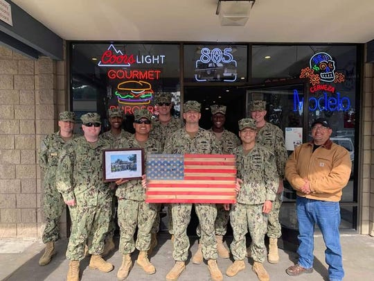 Military personnel pose outside Boar's Breath Grill in Port Hueneme before the coronavirus banned indoor dining. A customer left a $500 tip on Thursday to help the grill through the crisis.