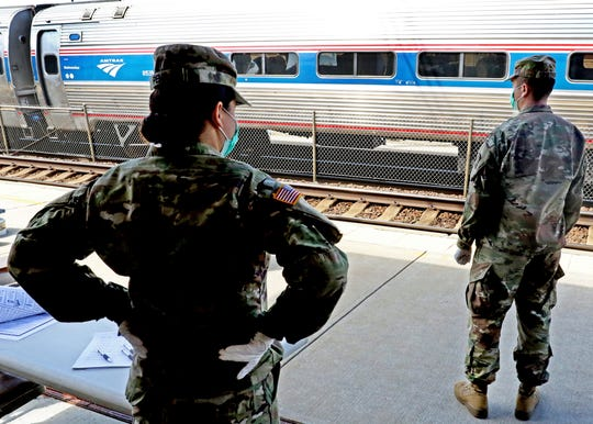 Members of the 1207th Rhode Island National Guard unit stand at the Westerly, R.I., Amtrak station Friday, March 27, 2020, to inform passengers from New York of the 14-day quarantine restrictions if disembarking in Rhode Island ordered by Gov. Gina Raimondo. At the time of the photo, no passengers had disembarked at the station.