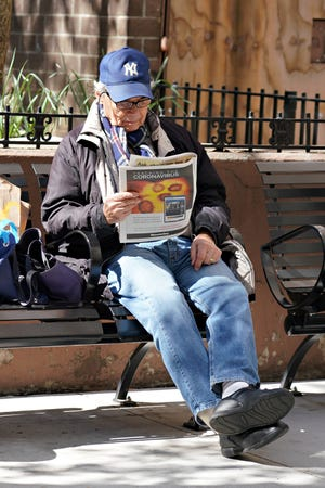 A man in New York sits on a bench reading a newspaper with 'Tracking the Coronavirus' visible on the page as the coronavirus continues to spread across the United States.