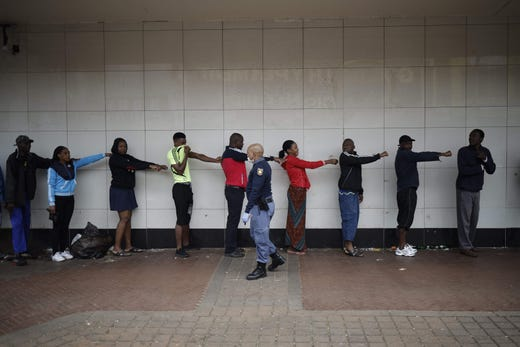 A member of the South African Police Service enforces social distancing as he makes shoppers hold their hands out in front of them to ensure that they are at least one meter apart from one another while they wait outside a supermarket in Yeoville, Johannesburg, on March 28, 2020.