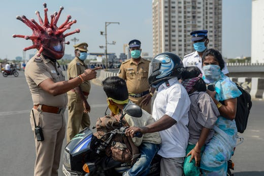 Police inspector Rajesh Babu, wearing coronavirus-themed helmet, speaks to a family on a motorbike at a checkpoint during a government-imposed nationwide lockdown as a preventive measure against the COVID-19 coronavirus in Chennai, India, on March 28, 2020.