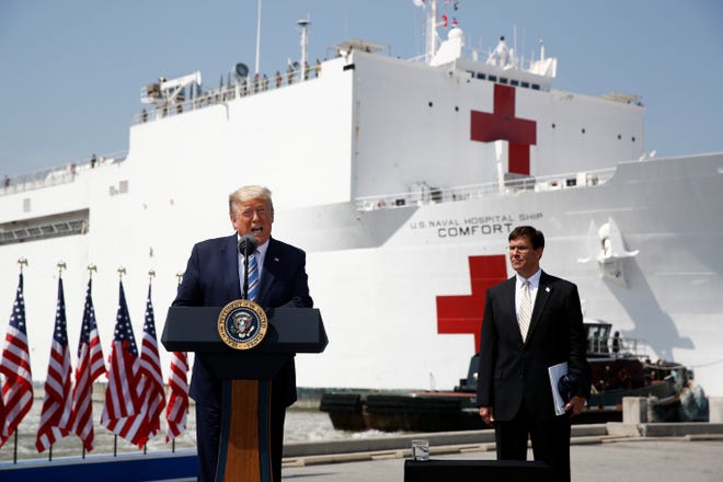 President Donald Trump speaks in front of the U.S. Navy hospital ship USNS Comfort at Naval Station Norfolk in Norfolk, Va., on Saturday. He is accompanied by Defense Secretary Mark Esper.