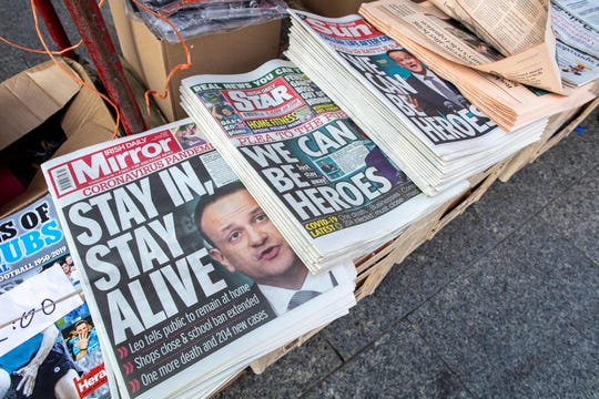 The front pages of Irish national newspapers, featuring a story about new measures introduced by Ireland's Prime Minister Leo Varadkar to help stem the Covid-19 pandemic, are pictured in a store in Dublin.