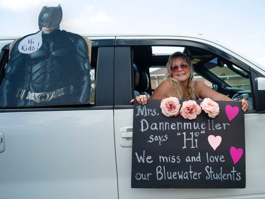 "Teacher Julie Dannenmueller holds her sign for the students with the help of the Caped Crusader as teachers from Bluewater Elementary school have a parade through their school's neighborhoods to sat ""hi"" to their homebound students on March 27, 2020 in Niceville, FL."