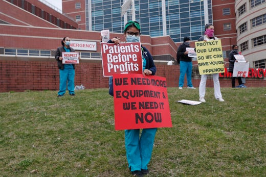 Nurses stand on a hill outside the emergency entrance to Jacobi Medical Center in the Bronx borough of New York, Saturday, March 28, 2020, as they demonstrate with members of the New York Nursing Association in support of obtaining an adequate supply of personal protective equipment for those treating coronavirus patients. A member of the New York nursing community died earlier in the week at another New York hospital. The city leads the nation in the number of coronavirus cases. Nurses say they are having to reuse their protective equipment endangering patients and themselves.