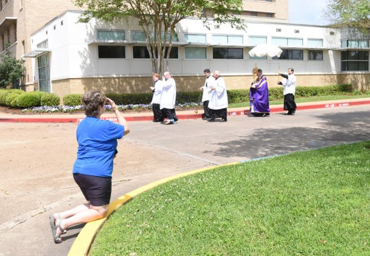 Father Chad Partain of St. Frances Cabrini Church, leads a Eucharist procession Sunday to CHRISTUS St. Frances Cabrini Hospital to conduct a blessing for those who are ill and for the doctors, nurses and other medical staff.