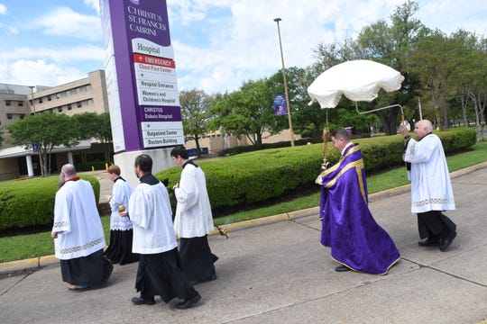 Father Chad Partain of St. Frances Cabrini Church, leads a Eucharist procession to CHRISTUS St. Frances Cabrini Hospital to conduct a blessing for those who are ill and for the doctors, nurses and other medical staff.