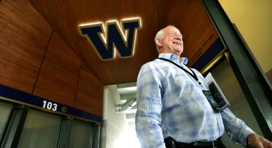 FILE - In this Aug. 28, 2013 file photo former head coach Jim Lambright smiles as he stands at a concourse entrance in the newly renovated Husky Stadium in Seattle. Lambright has died at age 77, the school announced on Sunday, March 29, 2020. Lambright spent nearly four decades associated with the Washington program as a player, assistant coach and head coach. (AP Photo/Elaine Thompson, file)