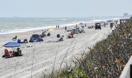 A sheriff's deputy patrols the beach near Canova Beach Park in unincorporated Brevard County Saturday. Unlike surrounding communities, the county did not close it's beaches this weekend between 11am and 4pm due to the coronavirus pandemic. Mandatory Credit: Craig Bailey/FLORIDA TODAY via USA TODAY NETWORK