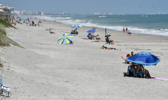 People relax on the beach near Canova Beach Park on Saturday afternoon in unincorporated Brevard County, just outside Melbourne city limits. Melbourne City Council members said fewer people went to Paradise Beach within city limits this weekend.