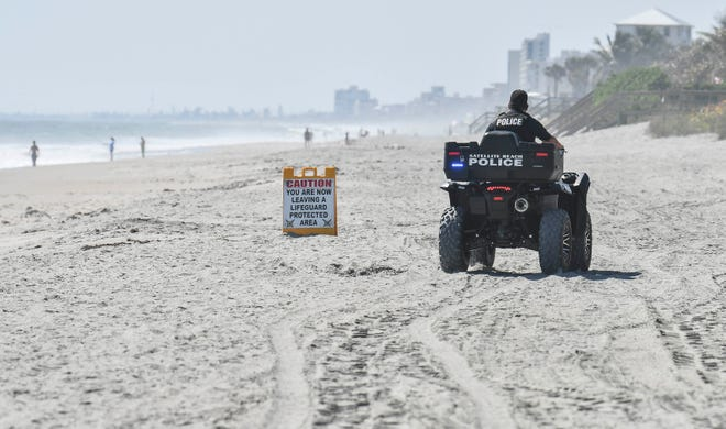 A Satellite Beach police officer patrols the sand March 28 near Pelican Beach Park after city officials closed the beach between 11 a.m. and 4 p.m. because of the coronavirus pandemic.
