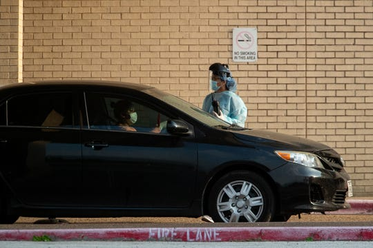Heath care workers conduct COVID-19 testing at Corpus Christi's drive-thru testing center at the old CHRISTUS Spohn Memorial Hospital parking lot on Sunday, March 29, 2020.