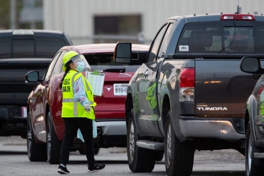 Cars lineup outside the old CHRISTUS Spohn Memorial Hospital at Corpus Christi's drive-thru COVID-19 testing center on Sunday, March 29, 2020.