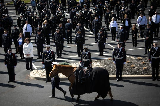 A riderless horse passes by local police officers during a ceremony for fallen Springdale Officer Kaia Grant prior to her funeral service at Vineyard Church on Sunday, March 29. Grant was killed in the line of duty Saturday, March 21, following a police chase and crash on Interstate 275. She was a 2005 graduate of Wyoming High School.