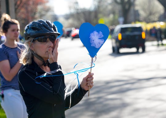Carrie Smith, Wyoming High School teacher, holds a heart while wiping away a tear during the funeral procession for fallen Springdale Police Officer Kaia Grant leaves in Wyoming on Sunday, March 29, 2020. Grant was killed in the line of duty Saturday, March 21, following a police chase and crash on Interstate 275. She was a 2005 graduate of Wyoming High School.