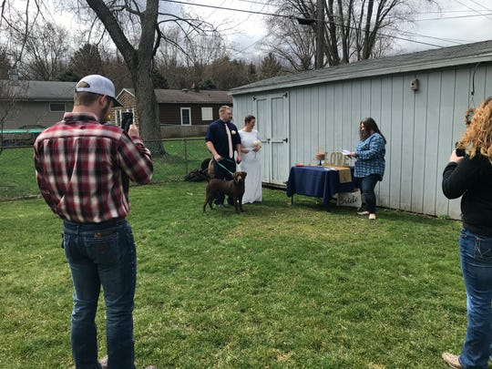 Andrew Czuk, 31, and Shawna Phillips, 33, of Eau Claire are married by Michelle McCoy of Coloma as witnesses (right) Taylor Brink, 20, of St. Joseph and (left) Bryant Miller, 28, of Buchanan look on. Chuck, the 2-year-old lab, was the best dog. After restrictions put in place by the government over concerns of the coronavirus pandemic derailed the couple's wedding plans, they opted for a small ceremony in McCoy's backyard.