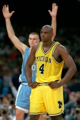 Michigan's Chris Webber stands by as North Carolina's Eric Montross celebrates during North Carolina's technical foul shots in the final seconds of the NCAA championship game in 1993.