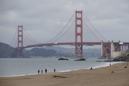 A small group of people walk in front of the Golden Gate Bridge at Baker Beach in San Francisco, Saturday, March 28, 2020, amid the COVID-19 coronavirus outbreak.