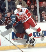 Red Wings center Steve Yzerman, left, leaves his feet to hit Avalanche winger Milan Hejduk during Detroit's 5-3 victory at Joe Louis Arena in 1999.