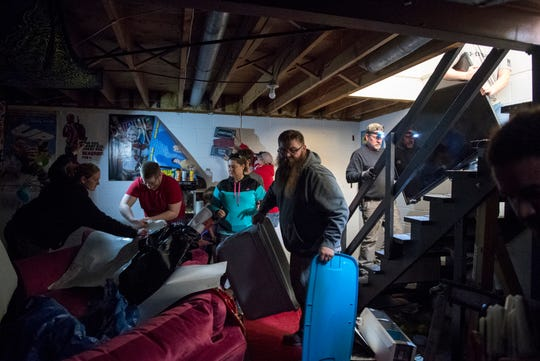 Family, friends and coworkers from Toyota Motor Manufacturing Indiana work to clear the basement at the Moseby residence off Sharon Road after wind ripped off the roof of the home Saturday evening, in Newburgh, Ind., Sunday afternoon, March 29, 2020. A tornado crossed the Ohio River from Kentucky and hit the Newburgh area, Saturday night, tearing roofs off homes and toppling trees and power lines.