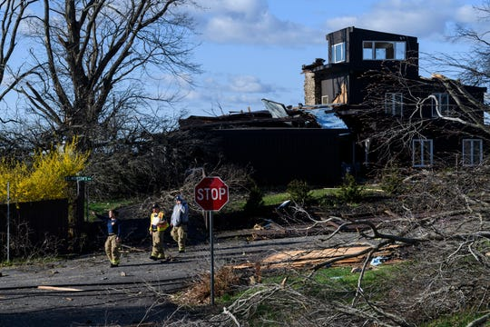 Emergency officials survey the storm damage on Jennings Streets in Downtown Newburgh, Ind., Sunday morning, March 29, 2020. A tornado crossed the Ohio River from Kentucky and hit the Newburgh area, Saturday night, tearing roofs off homes and toppling trees and power lines.