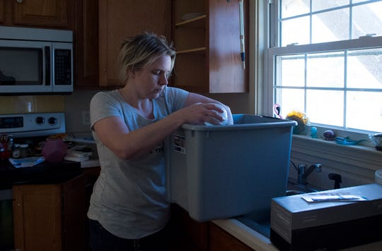 Melissa Mosbey packs up dishes from her kitchen as she works to clear belongs after winds ripped after winds Saturday night ripped the roof off their home off Sharon Road in Newburgh, Ind., Sunday afternoon, March 29, 2020. A tornado crossed the Ohio River from Kentucky and hit the Newburgh area, Saturday night, tearing roofs off homes and toppling trees and power lines.