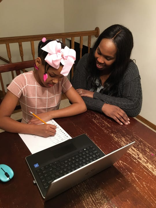 Madison Hobbs, 8, works on a homework assignment under the watchful eye of her mother, Stacy Hobbs. Madison also works with a tutor, St. Norbert College education major Chloe Stefflel, through a program that is paring tutors from four Wisconsin colleges with hundreds of K-12 students.