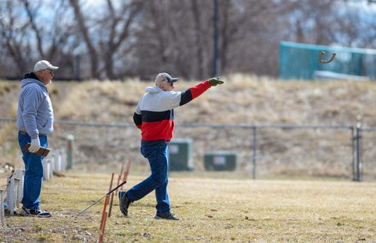 Butch White, left and Bob Rosteck play horseshoes at Elk's Riverside Park. Enjoy the warm weather while it lasts: A winter storm is expected this weekend.
