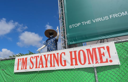 """A dummy, decorated in clothing and a mask, is posed above an """"I'm staying home!"""" banner off Route 1 in upper Tumon, March 29, 2020."""
