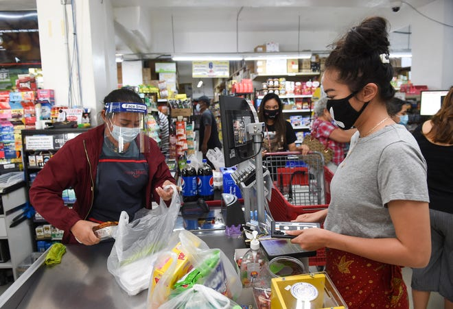 Cashier Renae Enriquez, wearing a resipirator and face shield, bags groceries for Kamille San Nicolas at Super Happy Mart in Barrigada, March 29, 2020.