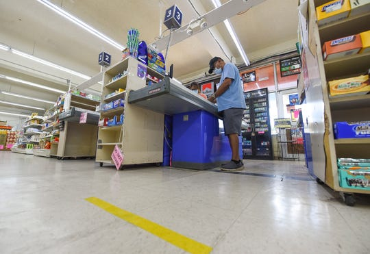 A yellow line on the Super Mart store floor indicates the implemented 6-feet social distancing policy, in Mangilao on March 29, 2020.