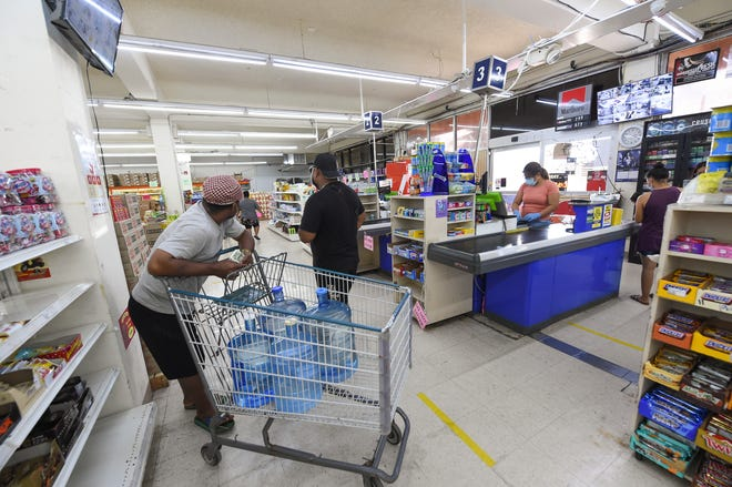 Customers line up in accordance with the store's social distancing policy at Super Mart in Mangilao in this March 29 file photo.
