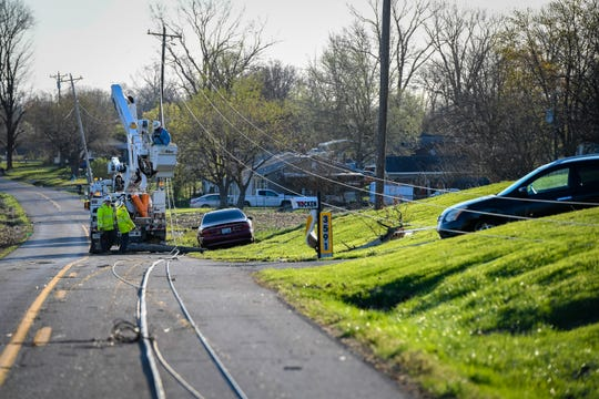 Utility workers repair downed power lines on Old Madisonville Road after a line of severe thunderstorms with tornado warnings passed through the area yesterday evening Sunday, March 29, 2020.