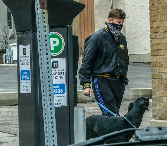 """Wearing a bandana for a face mask, a man walks his dog in the nearly empty streets of downtown Lansing this past weekend which marks the first week of a """"stay at home"""" order by Governor Gretchen Whitmer."""