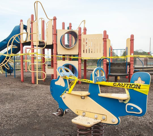 Playground equipment at Jonesboro's Allen Park is wrapped with caution tape to prevent usage in an effort to help slow the spread of the coronavirus on Friday.
