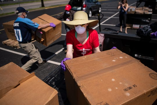 Volunteer Lindsey Kessler, center, unloads boxes of donated face shields during a personal protection equipment drive organized by Project C.U.R.E. outside of Nissan Stadium in Nashville, Tenn., Sunday, March 29, 2020. The collected equipment will be distributed to local medical facilities in need of supplies due to the COVID-19 pandemic.