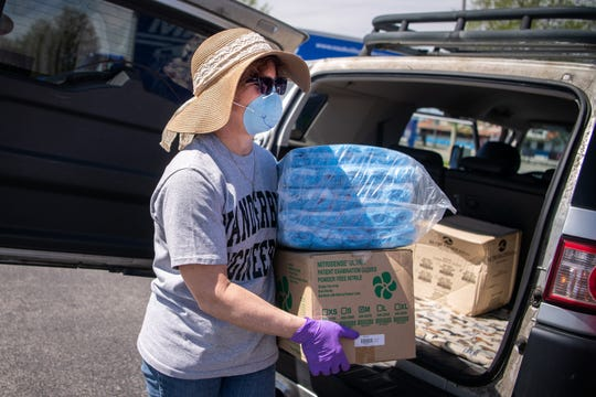 Volunteer Cynthia Paschal unloads donations from a car during a personal protection equipment drive organized by Project C.U.R.E. outside of Nissan Stadium in Nashville, Tenn., Sunday, March 29, 2020. The collected equipment will be distributed to local medical facilities in need of supplies due to the COVID-19 pandemic.