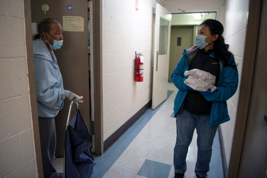 Volunteer Dora Valencia, of Paterson, on right, delivers free hot meals to senior citizens living in the Joseph Masiello Homes in Paterson who are too scared or unable to get out during the coronavirus pandemic. Valencia speaks with a resident about leaving her neighbors meals with her because the neighbor is not home. A group of volunteers organized by Paterson school teacher and community activist Zellie Thomas delivered close to 100 meals to seniors on Sunday evening March 29, 2020 in Paterson.